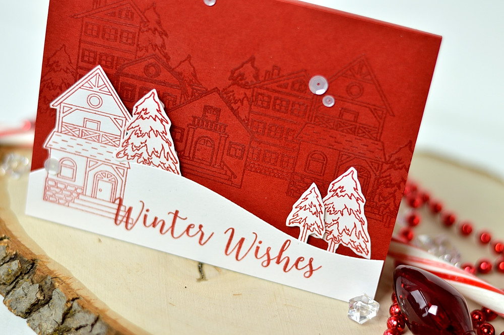 Create winter village scene by embossing holiday houses in the background. Card by @s_shayevich