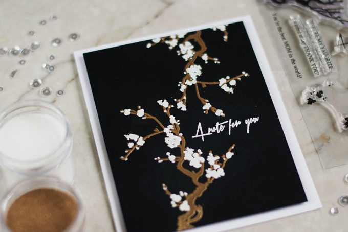 Altenew Under the Cherry Blossom Tree stamp set embossed in white and gold on black. Card by @craftwalks.