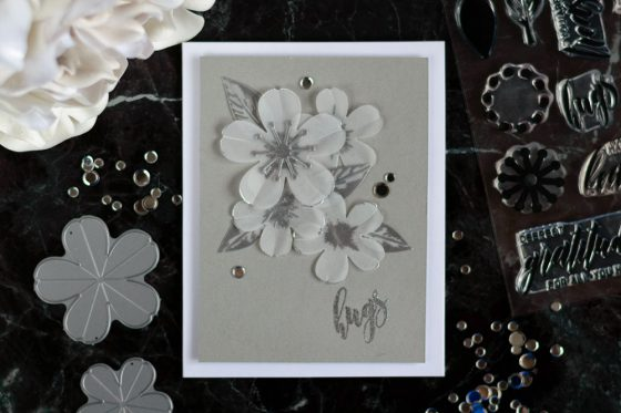 Create an elegant monochromatic card with Altenew Sakura Blossom Stamp Set applying silver embossing on vellum technique. Card by @craftwalks